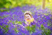 Adorable toddler girl with curly hair wearing a yellow dress playing with purple bluebell flowers