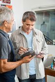Senior salesman holding electronic reader while man paying through smartphone in hardware store