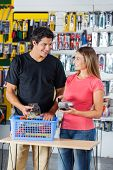 Smiling couple looking at each other while paying through credit card in hardware store