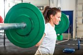 stock photo of fitness  - Side view of fit young woman lifting barbell in fitness box - JPG