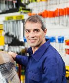Portrait of confident mature worker smiling in hardware shop