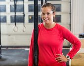 Portrait of confident young female athlete standing at cross training box
