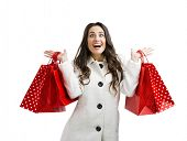 Beautiful happy woman holding shopping bags, isolated over a white background