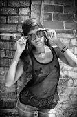 Woman wearing baseball cap, mesh top, sunglasses - city urban vice graffiti wall background