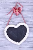 Heart shaped chalkboard on wooden background
