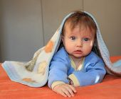 Charming blonde baby with blue eyes covered with a blanket looking at the camera