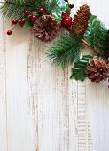 Christmas background with fir branches,pine cones and berries on the white wooden background