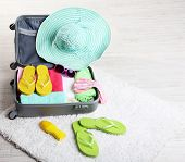 Suitcase with things on white carpet on the floor for travelling somewhere close to water for spendi