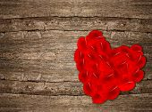 Heart Shaped Red Rose Petals On Wooden Background