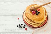 Stack of pancakes with honey and berries on wooden background.