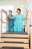 Portrait of male patient being assisted by nurse in moving upstairs