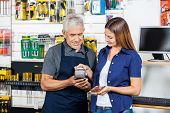 Senior salesman holding electronic reader while woman paying through smartphone in hardware store
