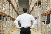 male manager man standing in big modern warehouse with back towards viewer