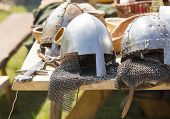 Medieval armor, helmets and swords lie on a wooden table, outdoor.