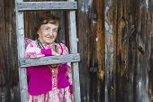 Grandmother in ethnic clothes in the yard of his rural home.