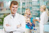 smiling male pharmacist chemist man portrait in pharmacy drugstore