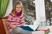 Cute Little Girl Reading A Book Sitting On The Window On Christmas Eve