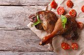 stock photo of roast duck  - two roasted duck legs with basil and tomatoes close up on an old table top view horizontal - JPG