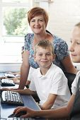 Male Elementary Pupil In Computer Class With Teacher