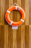 The Orange Life Buoy Hanging On The Wood Wall  For Safety And Rescue
