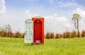 stock photo of outhouse  - The red toilet with white door open contrast with green grass and tree in the meadow and clear blue sky - JPG