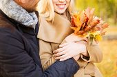 love, relationship, family and people concept - close up of smiling couple with bunch of leaves hugg