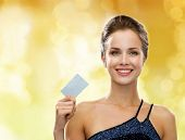 shopping, wealth, money, holidays and people concept - smiling woman in evening dress holding credit
