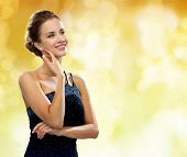 people, holidays and glamour concept - smiling woman in evening dress over black background over yel