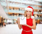 sale, gifts, christmas, holidays and people concept - smiling woman in red dress and santa helper ha