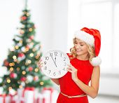 winter holidays, time and people concept - smiling woman in santa helper hat with clock over living