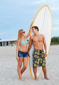 friendship, sea, summer vacation, water sport and people concept - smiling couple in swimwear and su