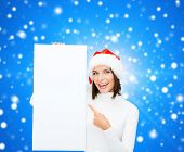 winter holidays, christmas, advertising and people concept - smiling young woman in santa helper hat