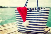 beach, summer, vacation, christmas and accessories concept - close up of beach bag and santa helper