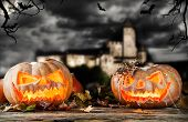Concept of halloween pumpkins on wooden planks. Blur scary castle on background
