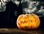Concept of halloween pumpkin on wooden planks. Blur scary church on background