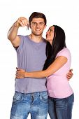 Young couple showing keys to house on white background