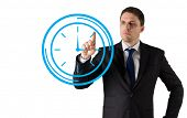 Composite image of businessman standing and pointing to a clock on white background