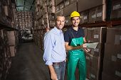 Warehouse manager smiling at camera with worker in a large warehouse