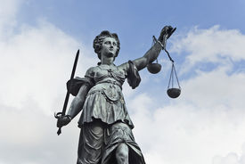 stock photo of cloudy  - Statue of Justice with sword and scales in front of a blue cloudy sky - JPG