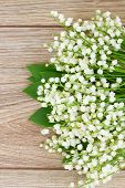 stock photo of lilly  - blooming lilly of the valley flowers posy on wooden background - JPG