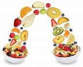 Flying Fruit Salad In Bowl With Fruits Like Apples, Oranges, Peach And Strawberry