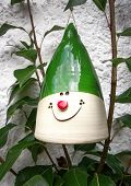 stock photo of conic  - A conical ceramic decoration with a smiling face and green pointed cap hangs in young pear branches against an exterior wall.