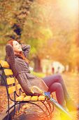 image of sitting a bench  - Style redhead girl sitting at bench in autumn park - JPG