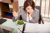 stock photo of lunch  - Busy young business woman eating a healthy lunch while working in her office - JPG