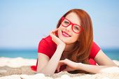 Redhead Girl In The Glasses On The Beach