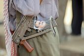 Man holds Kalashnikov machine gun, Hadramaut valley, Yemen.