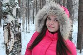 Young brunette posing in the snowy forest