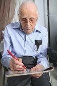 A elderly man sitting doing crosswords hobby