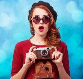 pic of beret  - Redhead women in beret with camera on blue background.