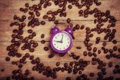 image of analog clock  - alarm clock and coffee beans on a wooden table - JPG
